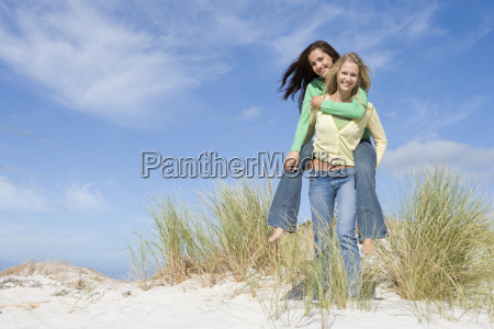 young woman giving piggyback ride to