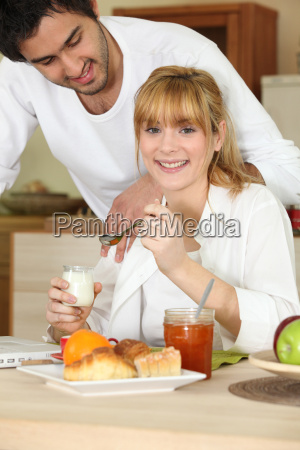 woman eating breakfast while her affectionate