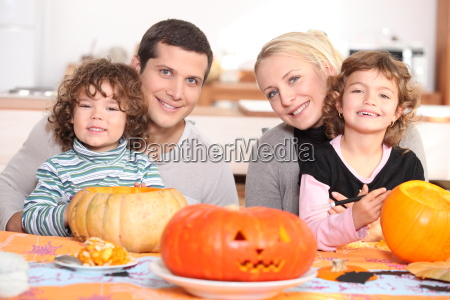 young family carving pumpkins