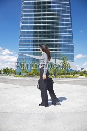 businesswoman walking next to skyscraper