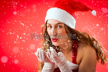 christmas woman blowing snow at christmas