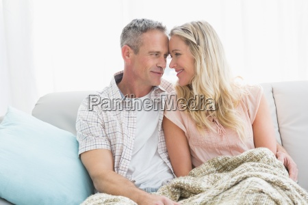affectionate couple sitting on sofa under