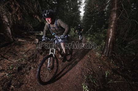 mountain bikers ride through the rain