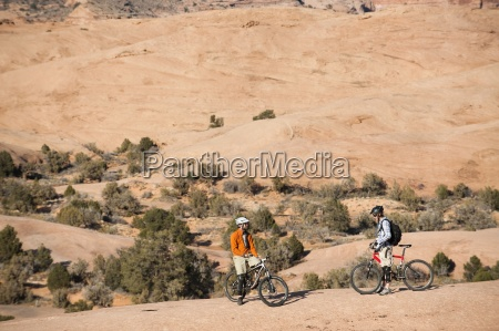 two mountain bikers rests during a
