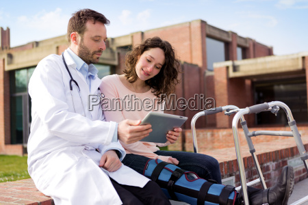 doctor showing reeducations tips on tablet