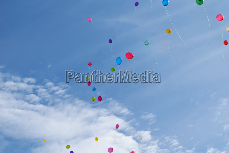 three multi colored balloons fly in