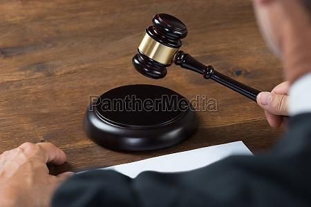 judge striking the gavel at table