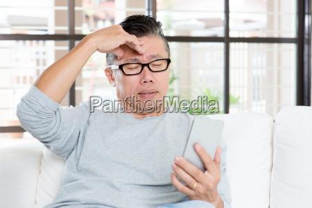 mature asian man headache while using