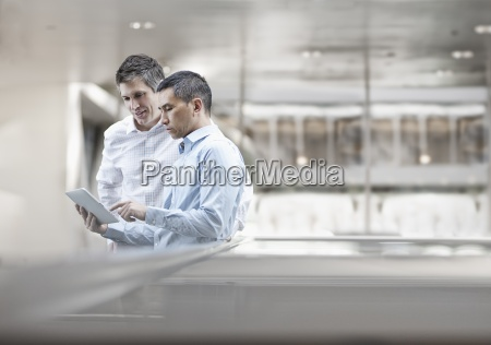two men business colleagues looking at
