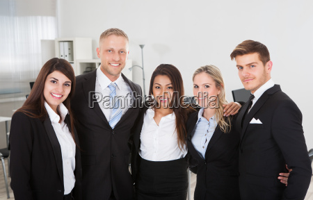 professionals standing arms around in office