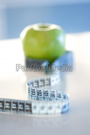 measuring tape wrapped around green apple