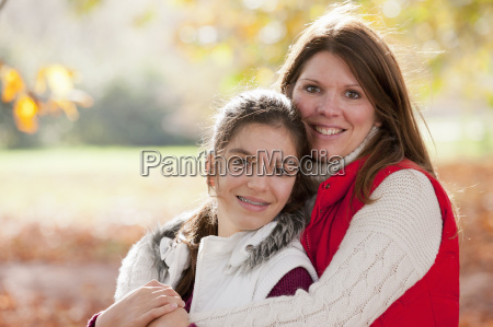 mother with arms around daughter looking