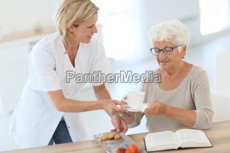 homecarer giving tea to elderly woman