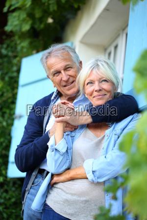 senior man embracing his wife at