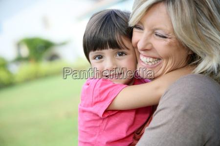 cheerful woman embracing little girl in