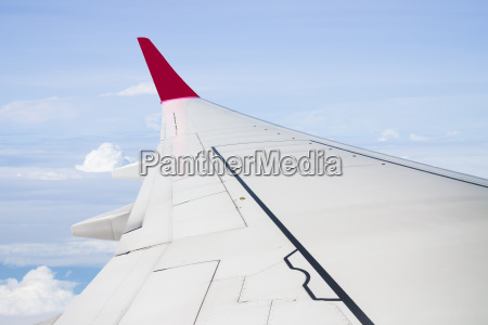 plane wing on cloudy blue sky