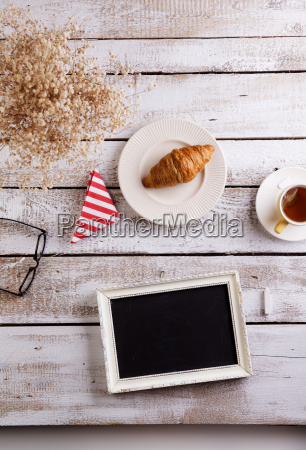 table with croissant tea and black