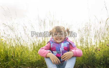 happy little girl sitting in front