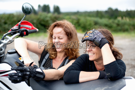 two female motorcyclists leaning on motorcycle
