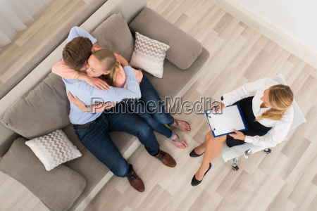couple sitting on sofa embracing in