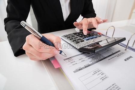 businesswoman hand calculating business report