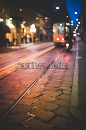 road with approaching tram at night