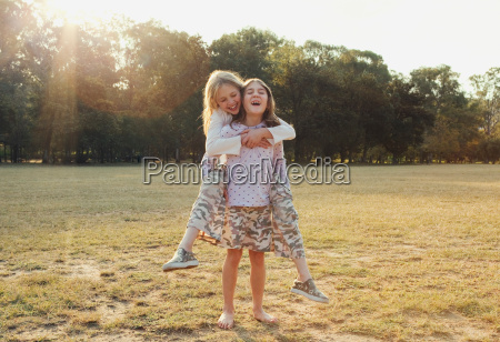 girl getting piggyback from sister