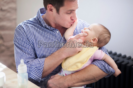 father cradling baby daughter