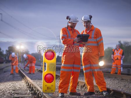 railway maintenance workers using digital tablet