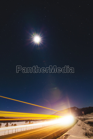 highway light trails and full moon