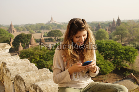 woman using smartphone on stone wall