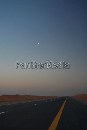 road through desert with moon in