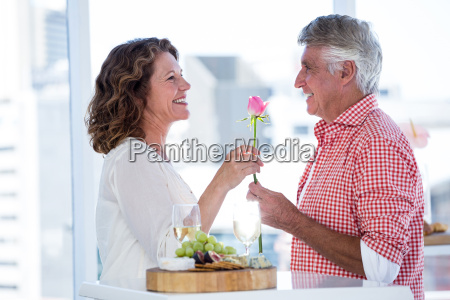 mature man giving flower to happy