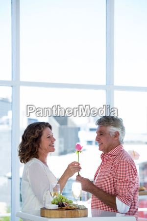 man giving flower to happy woman