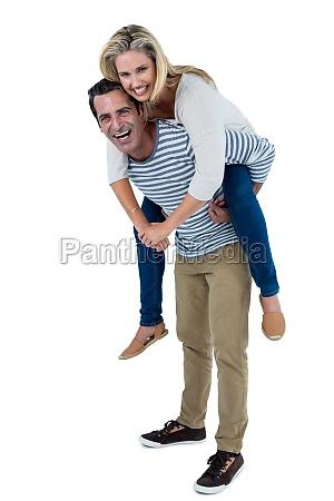 happy man carrying woman piggyback
