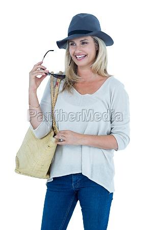 happy mid adult woman holding sunglasses