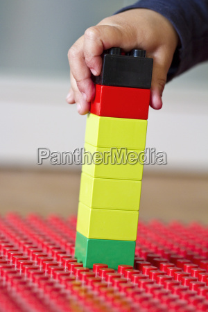human hand playing with lego bricks