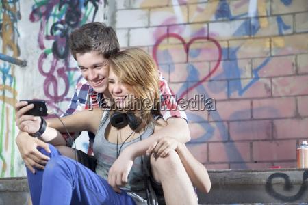 germany berlin teenage couple using mobile