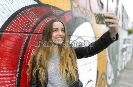 smiling teenage girl taking a selfie