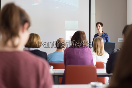 woman giving presentation in lecture hall