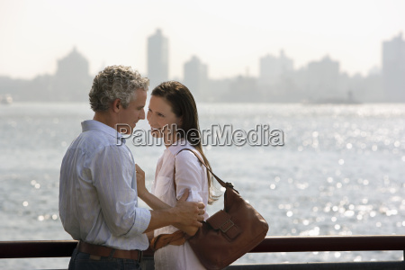 affectionate couple embracing by river