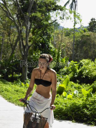 woman in bikini top riding bicycle