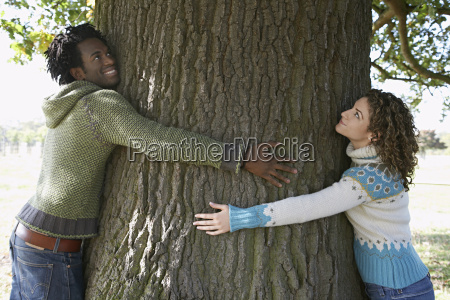young couple embracing tree trunk at