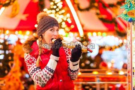 woman eating grilled sausage on christmas
