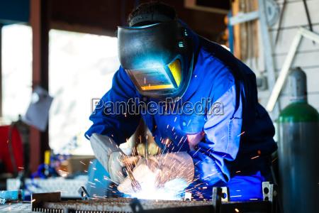 welder welding metal in workshop with
