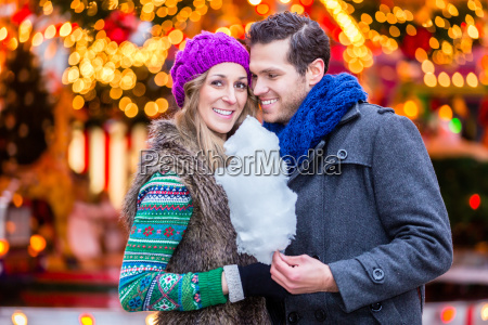 couple on christmas market eating cotton
