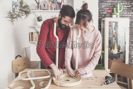 young couple assembling flat pack stool