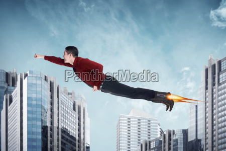 asian business man flying with rocket