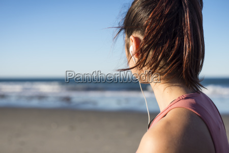 young woman with earbuds working out