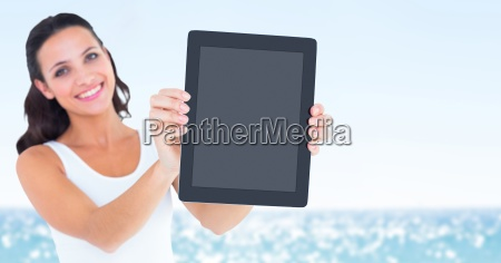 smiling woman holding out tablet against